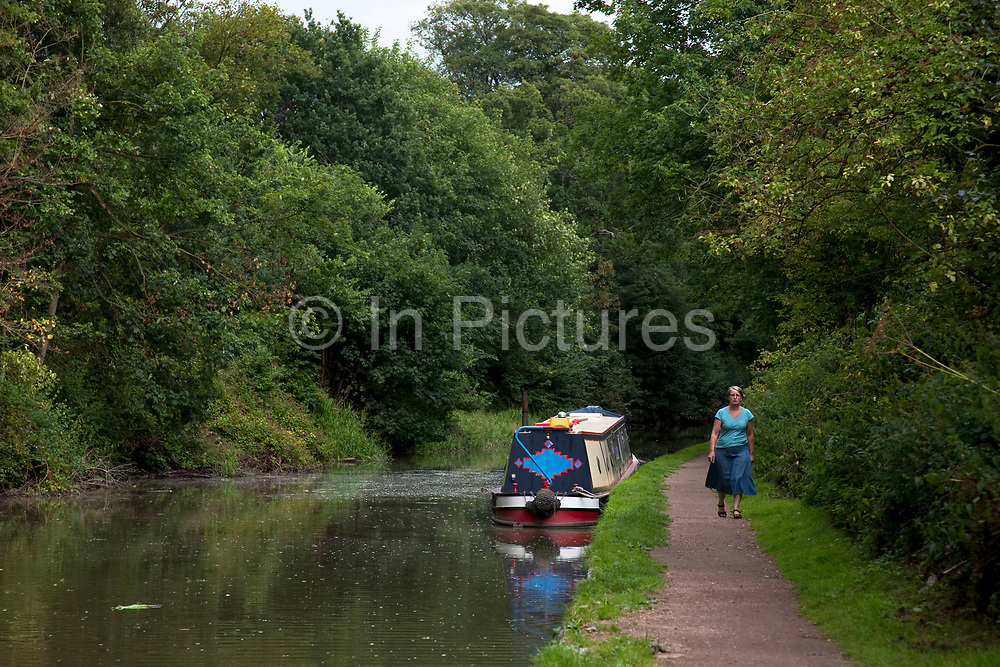Woman walks along the towpath of the Grand Union Canal at Hatton in Warwickshire.
