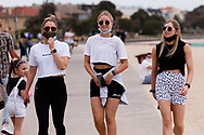 Three young girls walk together in St Kilda during the final days of the worlds toughest and longest COVID-19 restrictions in St Kilda.  With 21 days of zero new cases, Premier Daniel Andrews is expected to announce major easing of restrictions, including masks, at his press conference on Sunday. (Photo by Dave Hewison/Speed Media)
