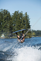 United States, Washington, Lake Sawyer, teen boy doing a wakeboarding jump.  MR