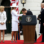 President of France Emmanuel Macron kisses the hand of first lady Melania Trump during an arrival ceremony to the South Lawn of the White House on Tuesday, April 24, 2018.