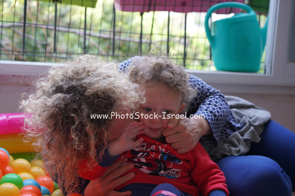 Young playful toddler boy with his mother