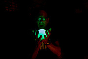 A man holds a glowing orb with spread fingers that shines up into his face and glasses. It is night-time and the man holds the sphere firmly in both hands as it appears as a ghostly apparition in his spectacles, as if haunted by a supernatural phenomena.