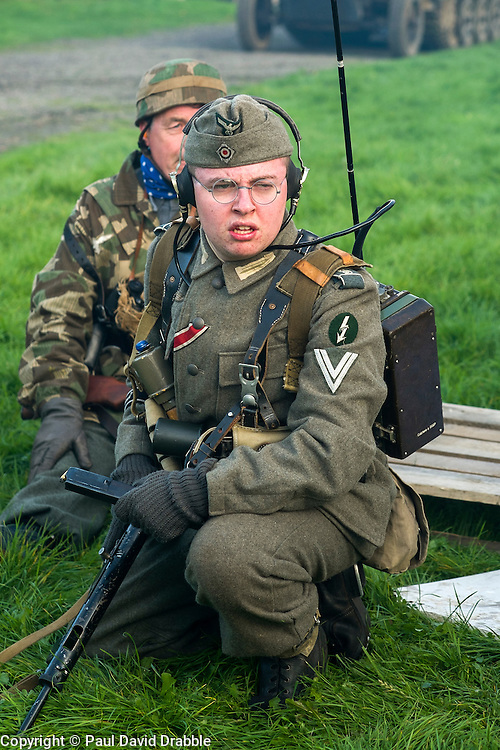 """A Re-enactor portraying a Obergefreiter of the Grossdeutschland Panzer Grenadier Division  during a battle battle re-enactment on Pickering Showground. He is wearing an Iron Cross 2nd Class ribbon and a """"Blitzbündel"""" or thunderbolt Badge on his sleeve above his rank marking him as a signals radio operator. He carrying a Field radio and is wearing a side cap and earphones"""