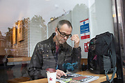 Photographer Richard Baker workingb from a cafe in London, United Kingdom.