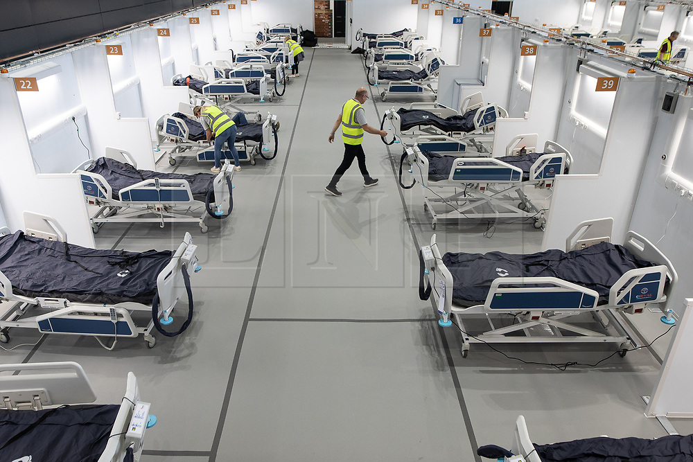 © Licensed to London News Pictures. 12/04/2020. Manchester, UK. The first patient bays to be populated with beds are checked and configured . The National Health Service is building a 648 bed field hospital for the treatment of Covid-19 patients , at the historical railway station terminus which now forms the main hall of the Manchester Central Convention Centre . The facility is due to open on Easter Monday , 13th April 2020 , and will treat patients from across the North West of England , providing them with general medical care and oxygen therapy after discharge from Intensive Care Units . Photo credit: Joel Goodman/LNP