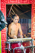 "19 AUGUST 2014 - BANGKOK, THAILAND:  A percussionist with the Lehigh Leng Kaitoung Opera troupe checks his drum before a performance at Chaomae Thapthim Shrine, a small Chinese shrine in a working class neighborhood of Bangkok. The performance was for Ghost Month. Chinese opera was once very popular in Thailand, where it is called ""Ngiew."" It is usually performed in the Teochew language. Millions of Chinese emigrated to Thailand (then Siam) in the 18th and 19th centuries and brought their culture with them. Recently the popularity of ngiew has faded as people turn to performances of opera on DVD or movies. There are still as many 30 Chinese opera troupes left in Bangkok and its environs. They are especially busy during Chinese New Year and Chinese holiday when they travel from Chinese temple to Chinese temple performing on stages they put up in streets near the temple, sometimes sleeping on hammocks they sling under their stage. Most of the Chinese operas from Bangkok travel to Malaysia for Ghost Month, leaving just a few to perform in Bangkok.        PHOTO BY JACK KURTZ"