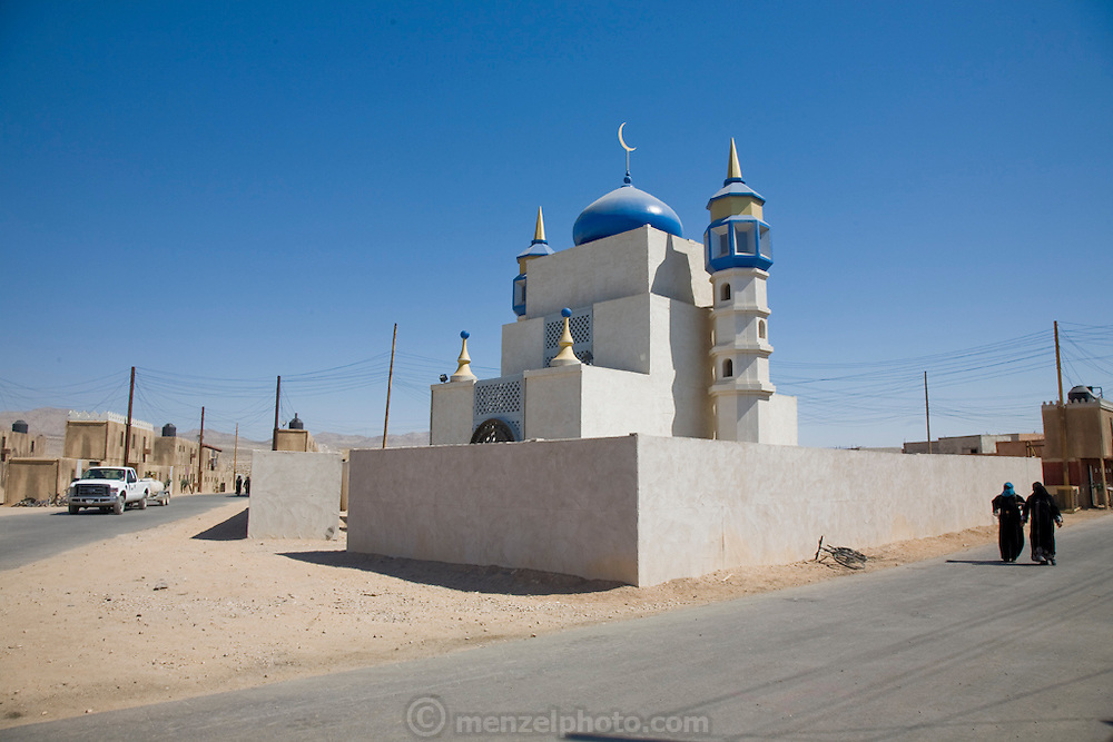 Women walk past a mosque in the fabricated Iraqi village of Medina Wasl at Camp Irwin, California. The village is used for training soldiers deploying to Iraq.