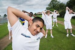 Group of secondary school students stretching before a PE class,