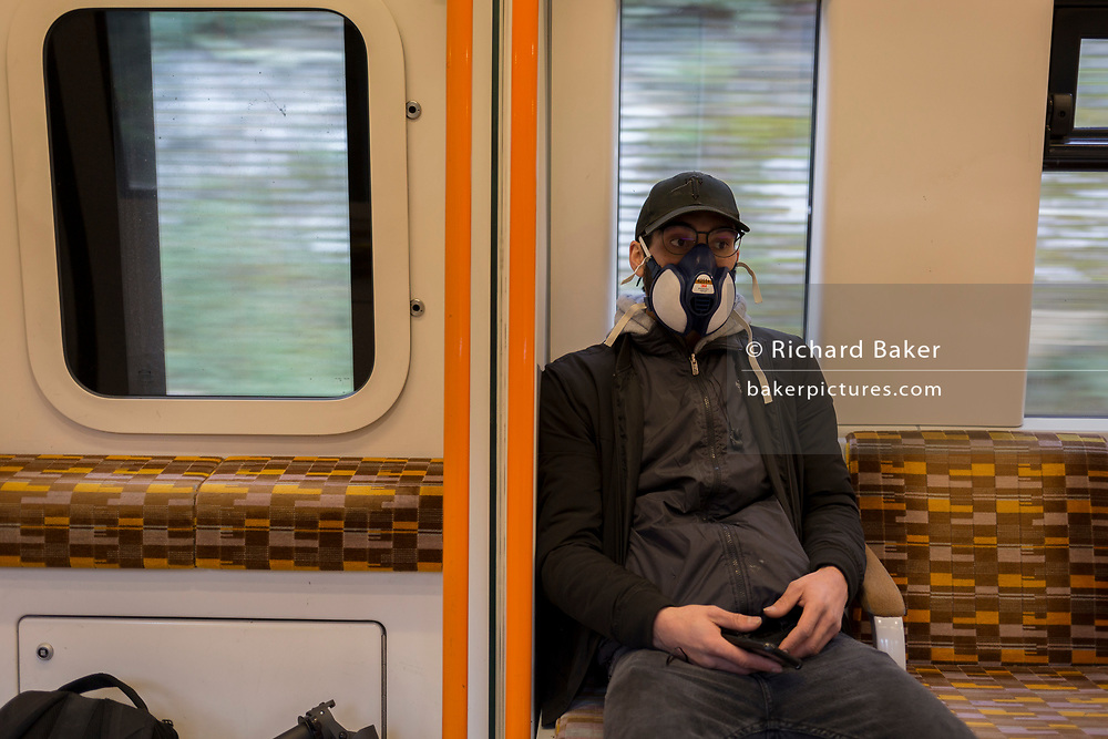 """As the UK government announces further Coronavirus-related restrictions to its citizens, with the immediate closure of pubs, cafes, gyms and cinemas, and the worldwide number of deaths reaching 10,000 with 240,000 cases, 953 of those in London alone, a male rail passenger wears an industrial maintenance free face mask made by 3M, a variety that gives """"Effective and comfortable protection against organic vapour and hazardous particulates"""", on an Overground train travelling across south London, on 20th March 2020, in London, England."""
