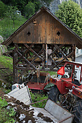A communist-era tractor is parked next to a traditional Slovenian village barn, on 18th June 2018, in Bohinjska Bela, Bled, Slovenia.