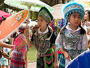 A group of young Hmong ethnic minority girls wearing traditional costumes and holding decorative umbrellas before their dance performance at the Women's International Group (WIG) bazaar, Vientiane, Lao PDR. The WIG Bazaar is a charity event aiming to raise funds for projects benefitting Lao women and children.