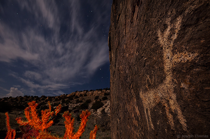 """""""Imagine if we could speak to the earliest Americans. In a way, they are speaking to us. Through their petroglyphs and pictograms, through the remnants of their dwellings, and through the other artifacts they left behind, they are sending us a prehistoric message that gives voice to the lives they once lived. The rock art of this remote canyon in Southeast Colorado was created up to 4000 years ago. Very little is known of the prehistoric Native Americans of the area, but archaeologists suspect they were nomadic hunter-gatherers whose visits were short as they followed migrating game.""""<br /> <br /> Getting the Shot: 3 O'clock in the morning brought the moon into perfect position to illuminate the canyon as well as this graphic message from the distant past. The cactus was lit by my LED headlamp passing through an orange filter for effect. The orange light on the cactus branches gives an appeanance reminiscent of flames from a primeval campfire, while the clouds above almost appear to be smoke from the fire mimicking the shape of the flames.<br /> <br /> Compositionally, this image does not allow the eye to move smoothly through the scene. Instead, there are three distinctive, sharply divided regions - the petroglyph wall, the cactus/canyon, and the night sky - each conveying its own mood and causing visual tension. At the same time the branches of the cactus, the fingers of clouds, and the points of the animal's antlers are all reaching skyward and provide a unifying theme for the image. I chose to make the rock wall nearly half of the frame in order to place emphasis on the petroglyph and the ancient people who created it."""