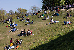 © Licensed to London News Pictures. 24/04/2021. London, UK. Members of the public relax during sunny weather in Greenwich Park in south east London. Temperatures are expected to rise with highs of 16 degrees forecasted for parts of London and South East England today . Photo credit: George Cracknell Wright/LNP