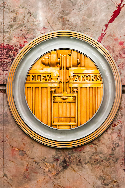 A machine-age, Art Deco, brass medallion, or roundel, on the Empire State Building's marble-walled lobby -- one of 11 such roundels, each honoring a different technology or craft essential to the construction of the great building. This one celebrates its elevators.