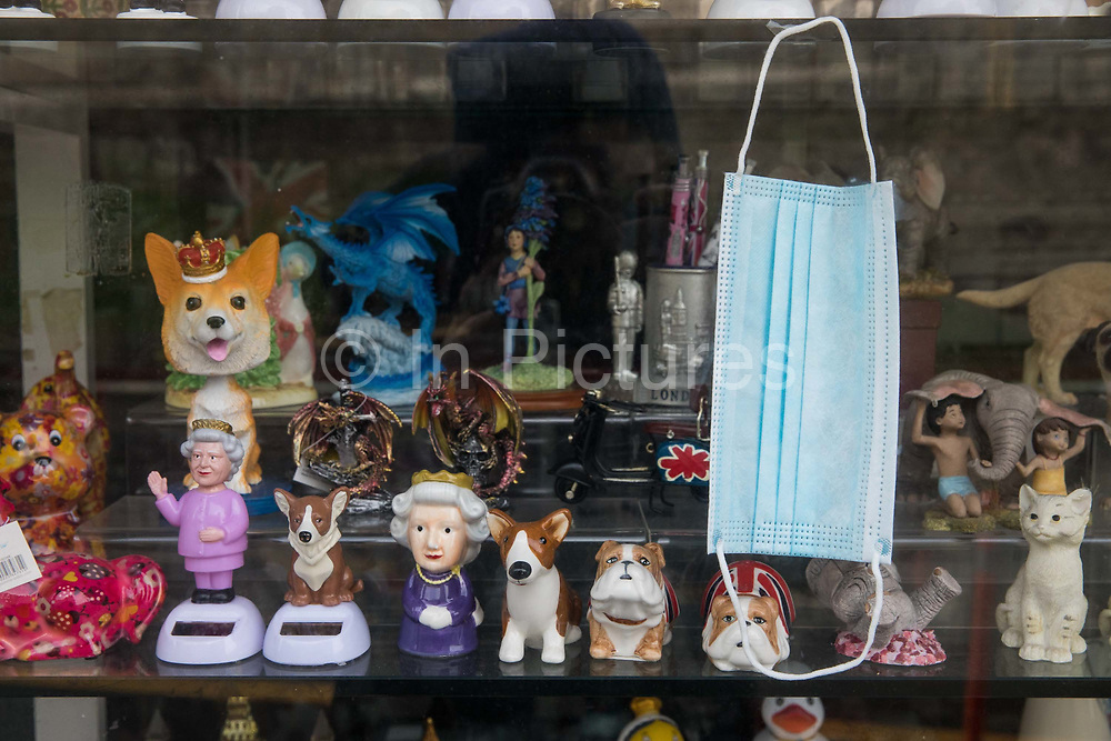 """A face covering and souvenirs are pictured in the window of a closed gift shop during the second coronavirus lockdown on 9th November 2020 in Windsor, United Kingdom. Only retailers selling """"essential"""" goods and services are permitted to open to the public during the second lockdown."""