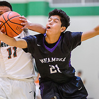 Wingate Bear Emerson Begay (11) collides with Miyamura Patriot Darin Baca (21) as he drives to the hoop Tuesday at Wingate High School.