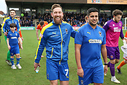 AFC Wimbledon midfielder Scott Wagstaff (7) walking out with adult AFC Wimbledon Mascot during the EFL Sky Bet League 1 match between AFC Wimbledon and Blackpool at the Cherry Red Records Stadium, Kingston, England on 22 February 2020.