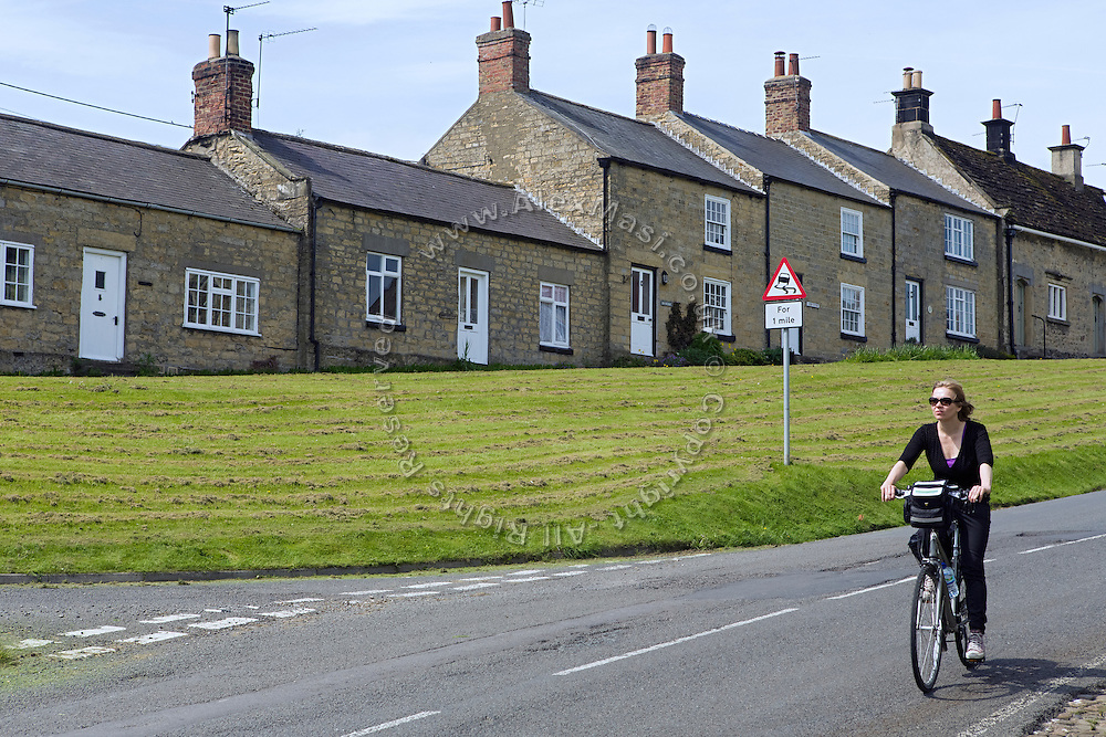A tourist is cycling in Coxwold, Yorkshire, England, United Kingdom.