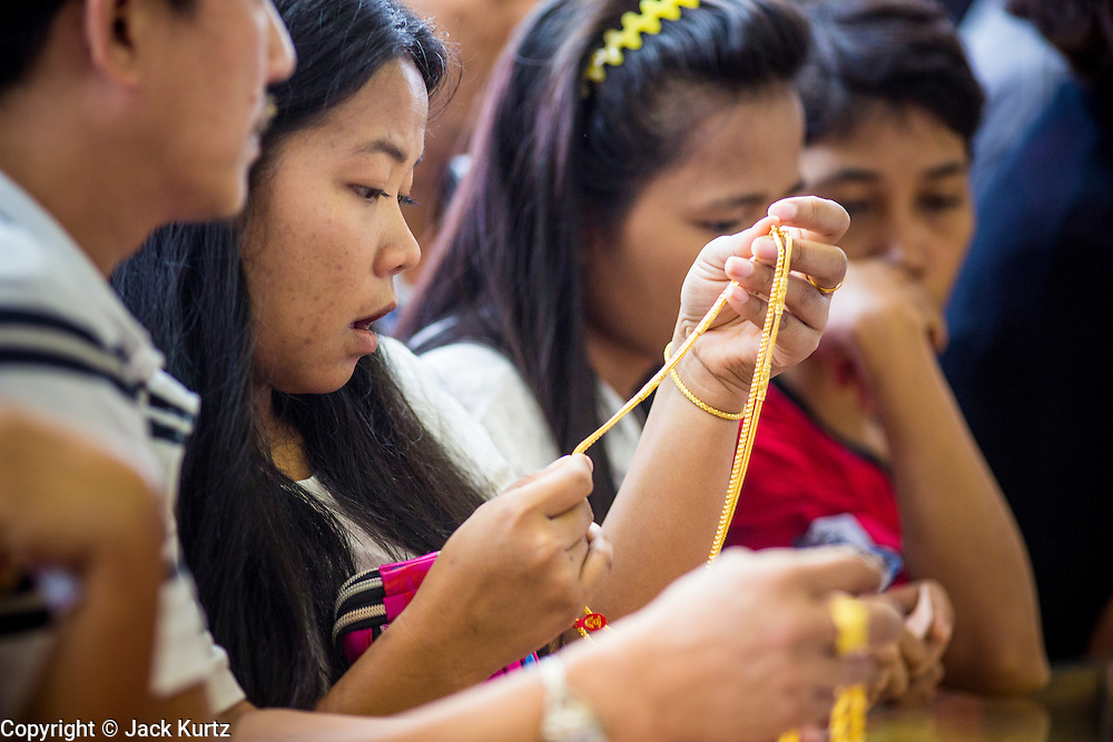 17 APRIL 2013 - BANGKOK, THAILAND:   A woman looks at a gold necklace she was buying in a Bangkok gold shop Wednesday morning. Thais flocked to gold shops in Bangkoks's Chinatown this morning to buy gold. Wednesday was the first day most gold shops were open after a five day holiday weekend. Shops were closed Friday through Tuesday, when global gold prices dropped by more than 13% based on jitters that Cyprus might liquidate its gold stocks. The Thailand Futures Exchange (TFEX) suspended trading of all gold and silver futures for a short time Tuesday morning because of instability in the market. Gold is now about 22 percent below the record peak of $1,920.30 an ounce set in September 2011. Thais buy gold as both jewelry and an investment, a hedge against inflation and financial failures. Bangkok's Chinatown district is the center of Thailand's gold trade.  PHOTO BY JACK KURTZ