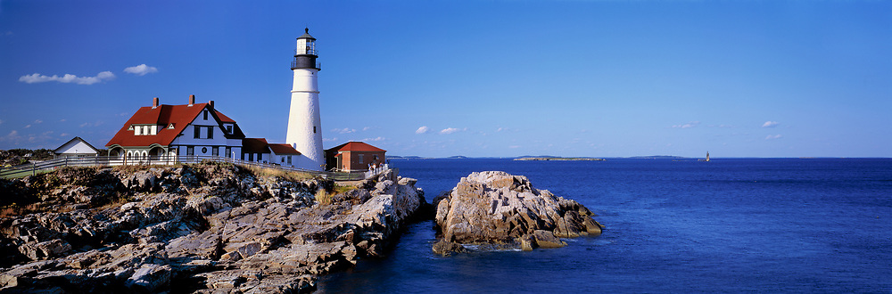 The white-washed Portland Head Lighthouse, in Maine, is contrasted by the deep blue of sea and sky, Maine.