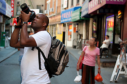 Photographer taking pictures on a Chinatown street in New York City