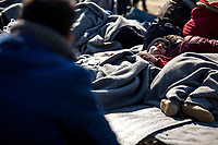 MYTILINI, GREECE - FEBRUARY 09: A refugee sleeps on the ground while waiting for registration at the Moria refugee camp on February 09, 2015 in Mytilini, Greece. After travelling for more than two hours crossing the Aegean sea, refugees are picked up by buses run by UNHCR and transferred to the Moria refugee camp where they have to register their names. As thousands of refugees arrive everyday in Lesvos, queues for registration can take up to two days. In the camp several international organisations provide assistance to the refugees as food, medical assistance, blankets and clothes among other items and services. Photo: © Omar Havana. All Rights Are Reserved