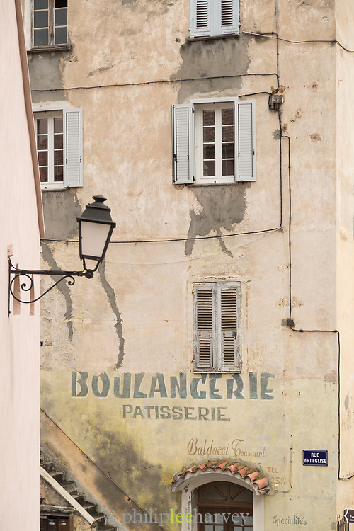 Old building with faded painted sign and windows, Corte, Corsica, France