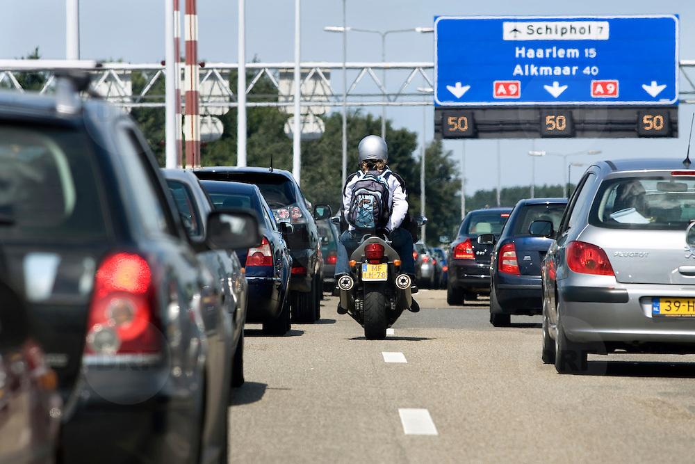 Nederland Amstelveen 8 juli 2007 Foto: David Rozing .File rijden op de A9 ter hoogte van Amstelveen / Ouder Amstel, motor rijder rijdt tussen de files door..Foto David Rozing