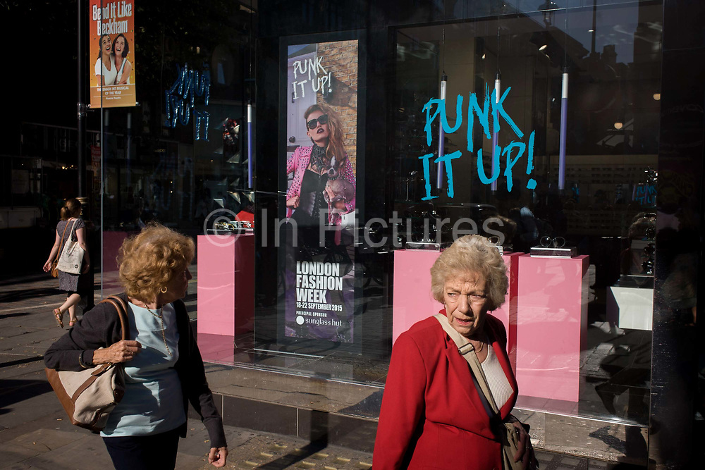 Two elderly ladies walk past a Sunglasses Hut shop whose theme is London Fashion Week's 'Punk it Up'. We see the older generation seemingly overwhelmed by the tastes and styles of young people today with the poster for the annual fashion festival advertising this year's theme. The ladies look left and right amid a world of brands and advertising, looking confused and worried, old and insecure.