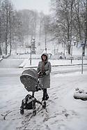 Tartu, Estonia - February 27, 2020: Geili pushes a pram as a beautiful snow falls in Tartu, Estonia.