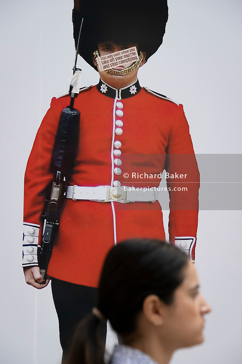 An unmasked shopper walks beneath the image of a guardsman whose face has been obscured by an anti-vaxx message mocking pandemic face coverings, on Covid 'Freedom Day'. This date is what Prime Minister Boris Johnson's UK government has set as the end of strict Covid pandemic social distancing conditions with the end of mandatory face coverings in shops and public transport, on 19th July 2021, in London, England.