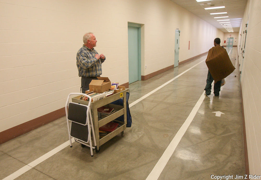 Chaplain Coyle talks with a prisoner passing in the halls as he heads for a cellblock as part of his ministry.