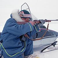 BAFFIN ISLAND, Nunavut, Canada. Inuit hunter Ham Kadloo shoots at a seal on frozen Eclipse Sound, north of Baffin Island.
