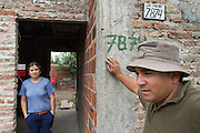 Raúl Moyano (right) and his wife Lidia Barrios stand in front of their home in Ocho de Mayo.