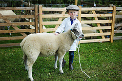 © Licensed to London News Pictures.29/07/15<br /> Borrowby, UK. <br /> <br /> A young girl holds her sheep as she prepares for her competition at the Borrowby Country Show and Gymkhana in North Yorkshire.<br /> <br /> Photo credit : Ian Forsyth/LNP