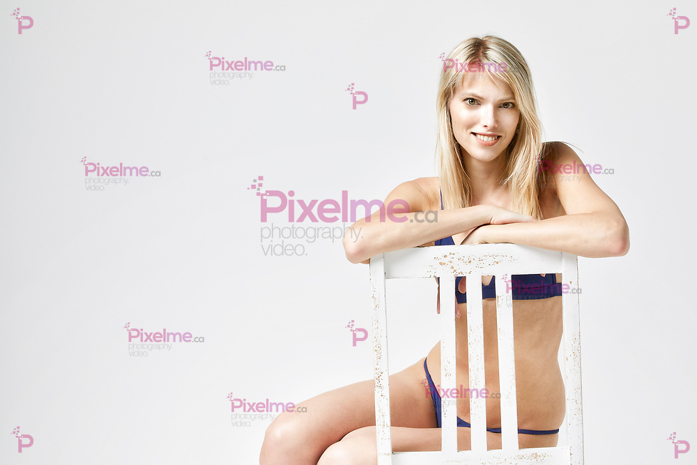 Portrait of a girl in bikini sitting over a white chair isolated in studio with a white background