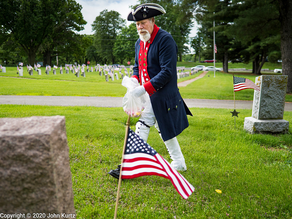 25 MAY 2020 - DES MOINES, IOWA: MIKE ROWLEY, a member of Sons of the Revolution, sprinkles flower petals on the graves of members of the Grand Army of the Republic (Union veterans of the US Civil War) in Glendale Cemetery in Des Moines on Memorial Day. Memorial Day is a federal holiday to honori and mourn the military personnel who have died while serving in the United States Armed Forces. Memorial Day is observed on the last Monday in May. In 2020, most public Memorial Day events in Iowa were canceled because of the COVID-19 pandemic.   PHOTO BY JACK KURTZ