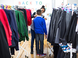 © Licensed to London News Pictures . Manchester , UK . Trying a new school uniform on . The Wood Street Mission is opening its community shop today (Tuesday 16th August 2016) , enabling families on a low income to get school uniform and other school necessities for free , in time for the new school year . Founded by Methodist Minister Alfred Alsop in 1869 , the Mission's aim is to alleviate the effects of poverty on children and families in Manchester and Salford . Photo credit : Joel Goodman/LNP