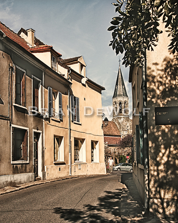 Narrow street in Louveciennes, France leads to the 13th century church in the main part of the village.  Aspect Ratio 1w x 1.25h.