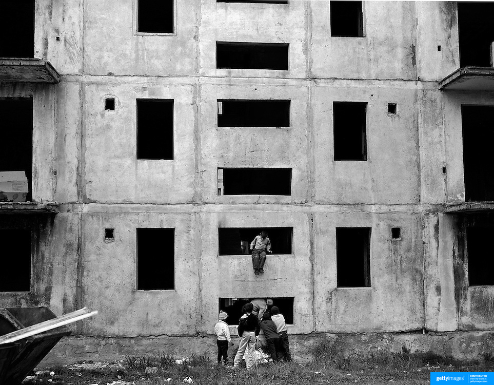 Children play in an unfinished communist style housing block which still stands in the heart of a housing estate in the small Romanian town of  Copsa Mica, Transylvania, Romania. Copsa Mica was once described as the most polluted town in Europe. May 9, 2008. Photo Tim Clayton...Copsa Mica, a small industrial town deep in Transylvania, Romania, was described during the 1990s as the most polluted town in Europe with lead levels reaching were more than 1000 times the allowable International limits and life expectancy nine years shorter than the National average...The pollution was caused entirely by two factories, Carbosin produced black for dies and tires and closed in 1993 while Sometra, a nonferrous smelter is still operational today...The pollution was so bad sheep were black, covered in soot and health officials advised against eating livestock or vegetables and drinking the water or milk...The Communist rule of Nicolae Ceausescu is blamed for the widespread environmental degradation that left industrial parts of Romania in ecological disaster. Industry was situated in a way to concentrate pollution in small areas leaving the rest of the country relatively free of pollution.Copsa Mica in particular was left an environmental disaster...The pollution caused a direct affect on human health with widespread Lung disease, Impotency, the highest infant mortality rate in Europe, Lead poisoning andbehavioral problems...Fifteen years on since the closure of Carbosin in 1993, the factory skeleton remains as part of the towns bleak landscape, Unfinished communist style housing blocks still stand in the heart of the towns housing estate. The town's inhabitants arestill trying to recover from the long lasting effects of pollution...Recent survey's found the soil contained so much lead that it was 92 times above the permitted level; the vegetation had a lead content 22 times above the permitted level. While toxins have penetrated at least one meter (three fe