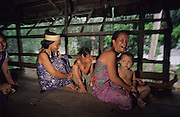 DAYAK LONGHOUSE, MALAYSIA. Sarawak, Borneo, South East Asia. Dayak, 'Kenyah', family on longhouse verandah. Tropical rainforest and one of the world's richest, oldest eco-systems, flora and fauna, under threat from development, logging and deforestation. Home to indigenous Dayak native tribal peoples, farming by slash and burn cultivation, fishing and hunting wild boar. Home to the Penan, traditional nomadic hunter-gatherers, of whom only one thousand survive, eating roots, and hunting wild animals with blowpipes. Animists, Christians, they still practice traditional medicine from herbs and plants. Native people have mounted protests and blockades against logging concessions, many have been arrested and imprisoned.