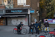 Kids and fish and chip shop. Street scene. East London