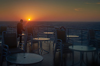A crew member setting up outdoor tables for breakfast at sunrise. Image taken with a Leica X2 camera.