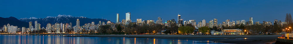 Panorama of Vancouver's English Bay, West End and Kitsilano. From the West End condo and apartment towers to the new Trump Tower and Living Shangri-La towers. Mountains in the background are Mount Bishop (left) and Mount Seymour.  Photographed from Kitsilano Beach Park in Vancouver, British Columbia, Canada.