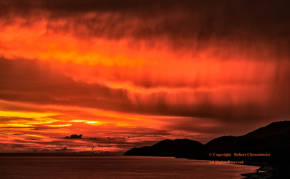 Fiery Shoreline: A fiery red sunset with the shoreline  mountains held in silhouette, as seen from the Castillo de San Pedro de la Roca fortress, Santiago de Cuba, Cuba