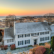 """This dawn real estate marketing image of a home overlooking the marsh and """"fish camps"""" in North Hampton was taken right before Christmas time. The home sits well below the road, and it is impossible to get a photo that shows both the front of the home and the distant ocean without going up about 20 feet above the road level."""