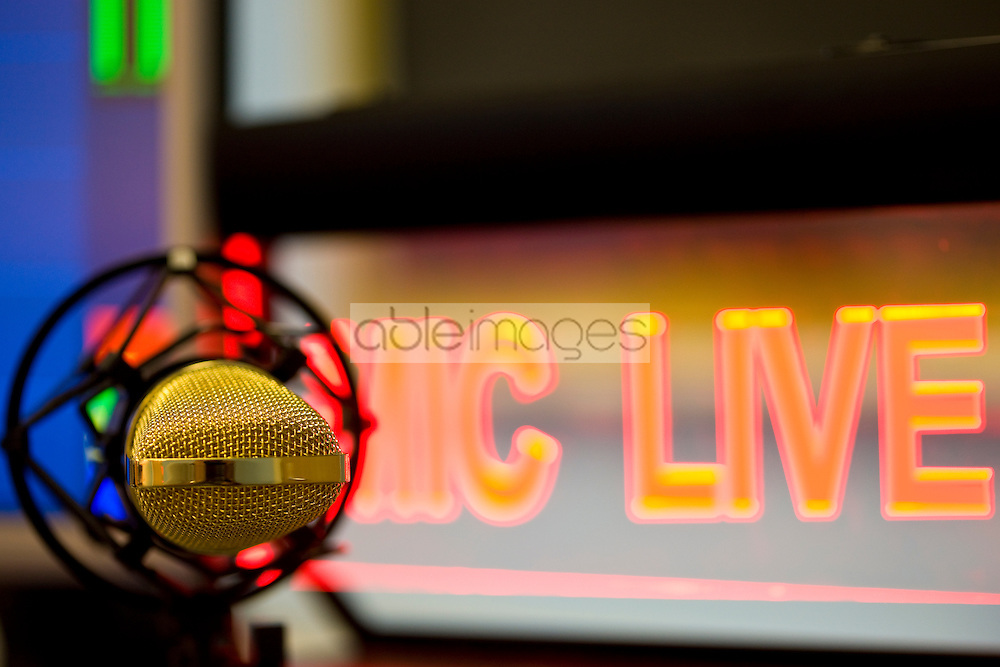 Close up of a gold microphone and illuminated sign