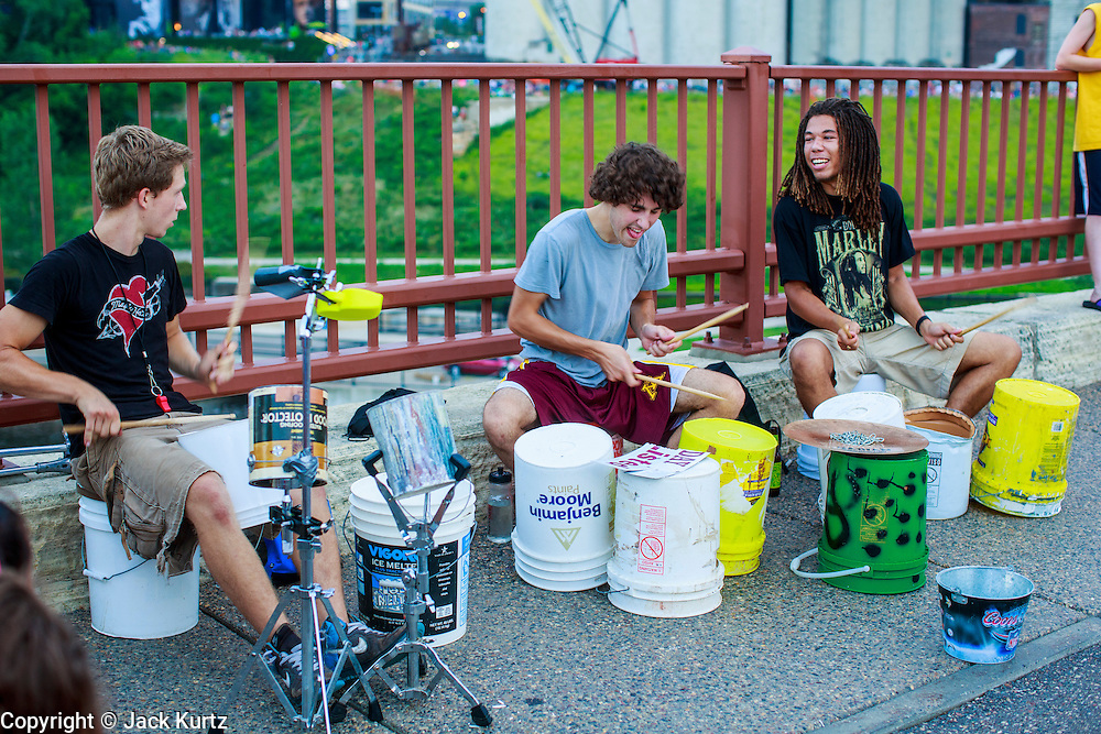 21 JULY 2012 - MINNEAPOLIS, MN:  Bucket drummers perform on the Stone Arch Bridge in Minneapolis, MN. The Stone Arch Bridge is a former railroad bridge crossing the Mississippi River at Saint Anthony Falls in downtown Minneapolis, Minnesota. Positioned between the 3rd Avenue Bridge and the I-35W Saint Anthony Falls Bridge,[2] the Stone Arch Bridge was built in 1883 by railroad tycoon James J. Hill for his Great Northern Railway, and accessed the former passenger station located about a mile to the west, on the west bank of the river. The structure is now used as a pedestrian and bicycle bridge. It is an Historic Civil Engineering Landmark, and was added to the National Register of Historic Places in 1971 as a part of the Saint Anthony Falls Historic District.   PHOTO BY JACK KURTZ