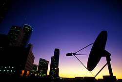 Stock photo of a satellite dish atop a roof in downtown Houston Texas