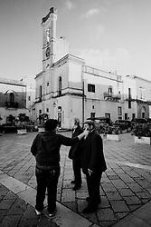 Reportage sviluppato ad Alessano (LE). Viene presa in considerazione fotograficamente, la gente che popola il paese nei suoi bar, piazze, strade, giardini pubblici. Ed, insieme a questa, i particolari caratterizzanti il luogo...Uomini scherzano in piazza.